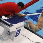 China's He bites on towel to aid his start in men's 50m Backstroke S5 race during the London 2012 Paralympic Games in the Olympic Park