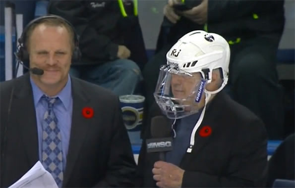 Rick Jeanneret wearing a helmet calling game from bench
