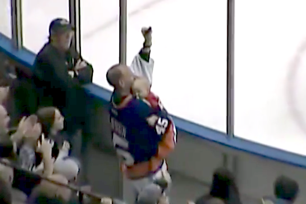 hockey fan catches puck while holding baby