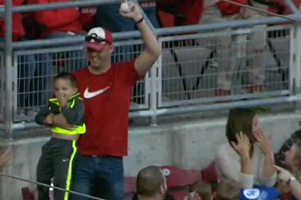 reds fan one-handed catch while holding kid