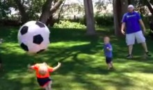 Dad Lays Out Child with a Comically Large Soccer Ball (Video)